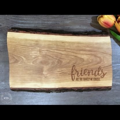 "Live edge board with ""friends are the family we choose"" engraved in the corner."