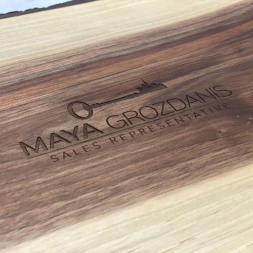 Realtor logo engraved on the back of a wholesale live edge charcuterie board.