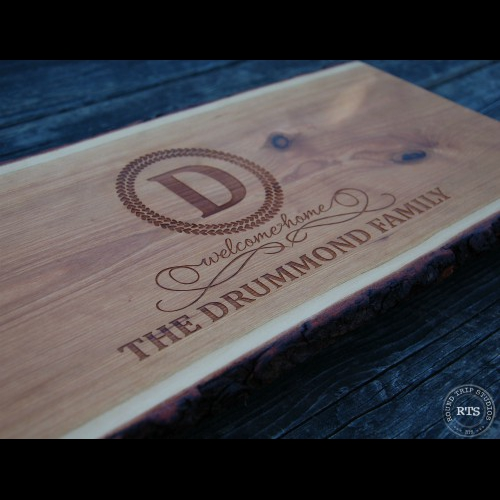 Live edge wood serving board with regal welcome home design engraved.