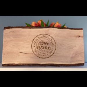 Serving board with tuscan our home design engraved on it.