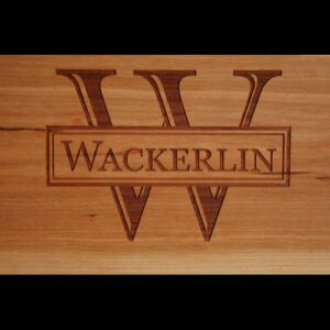Live edge wood serving board with initial and name engraved.
