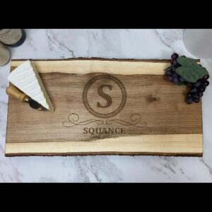 Live edge serving board with initial, name and date engraved in the center.