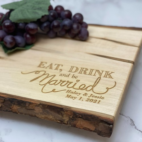 Eat, drink and be married engraved in the corner of a live edge serving board.