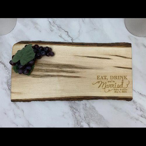 Live edge charcuterie board with wedding design engraved in the corner.