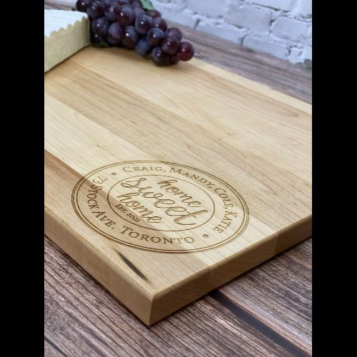 Tuscan home sweet home engraved in the corner of a rectangular cutting board.