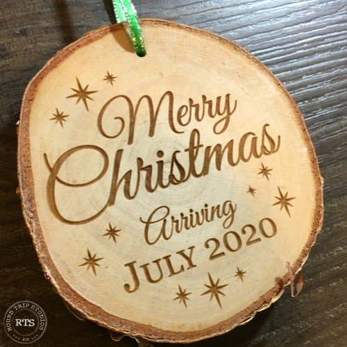 Pregnancy announcement engraved on rustic birch ornament.