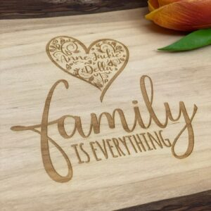 """Live edge serving board with """"family is everything"""" engraved. There is also a heart filled with the names of the family."""