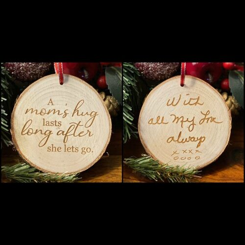 """Rustic birch ornament with handwriting on one side and the saying """"A Mom's hug lasts long after she lets go"""" on the other."""