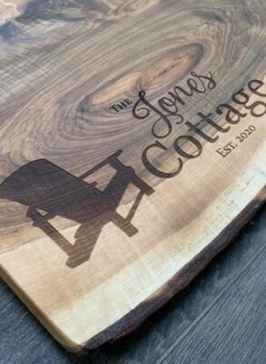 Close up of an abundance board with a muskoka chair and family name engraved.