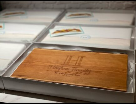Engraved live edge charcuterie board shown in packaging for a wholesale order.