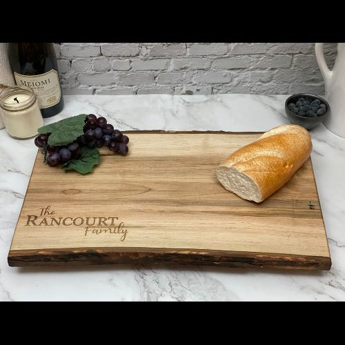 Live edge cutting board with a simple engraving of a family name in the corner.