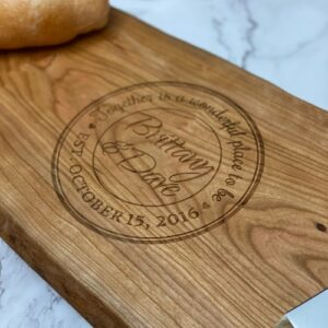 """LIve edge charcuterie board the name, date, and """"together is a wonderful place to be"""" engraved on it."""