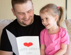 Dad and daughter holding a Father's Day card.