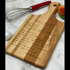 Handwritten recipe engraved on a paddle style cutting board.