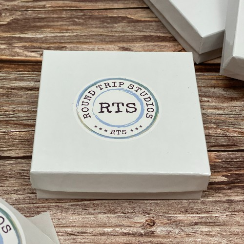 White gift box with logo sticker on the top.