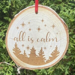 """Rustic birch ornament with """"all is calm"""" engraved on the front."""
