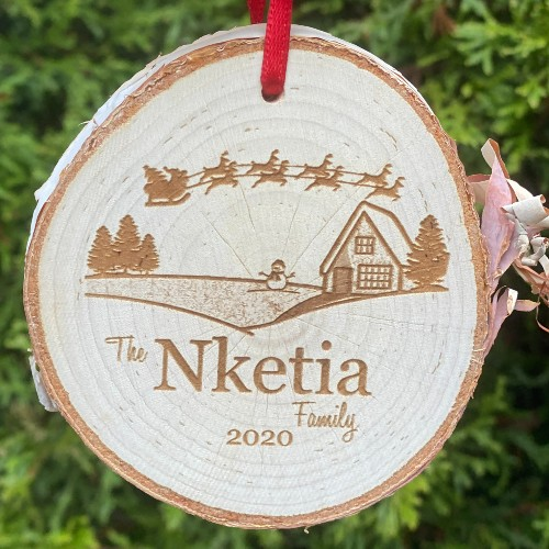 Rustic birch ornament with a house, snowman and santa flying overhead engraved.